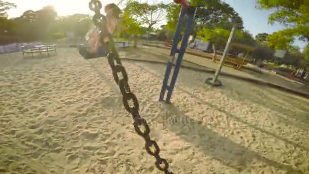 Dívka a chlapec houpání na houpačce