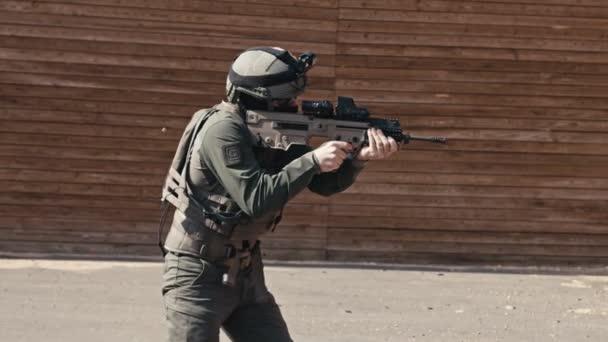Lassú mozdulat, ahogy egy katona automata puskát lő lőtávolba.