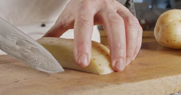 Zpomalený pohyb kuchaře krájejícího bramboru ostrým velkým nožem