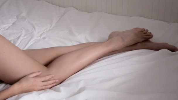 Nude female legs young girl lying in a white bed
