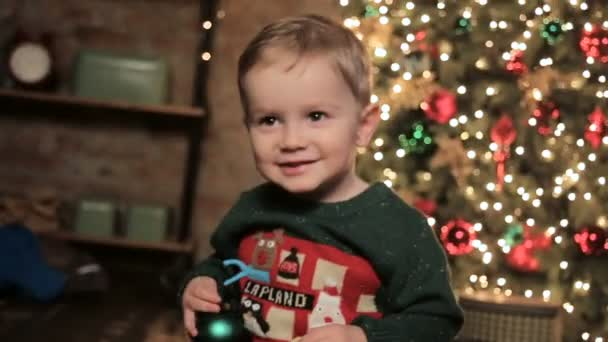 Junge sitzt neben Weihnachtsbaum