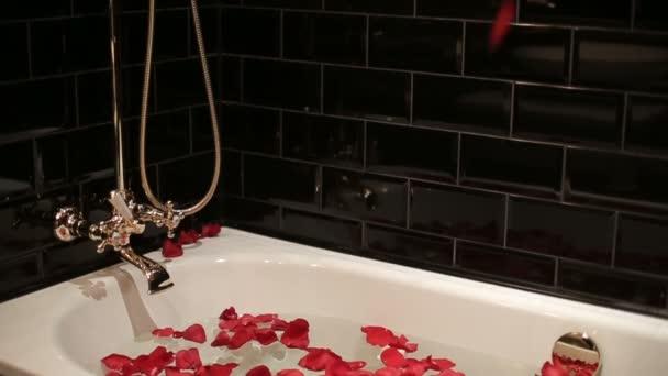 Salle de bain noir avec l'eau et de pétales de roses rouges