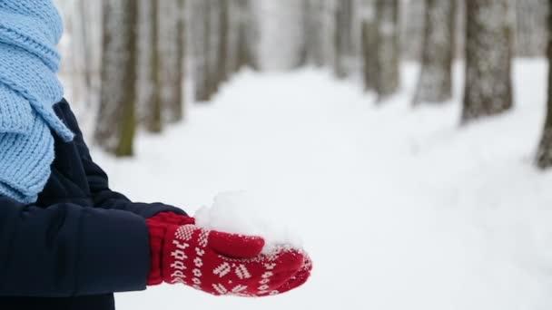 dívka stojící bokem hodí na sněhu se v červené rukavice