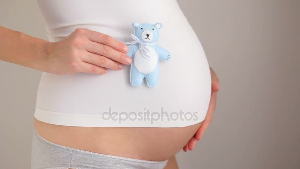 pregnant girl holding little bear toy blue color