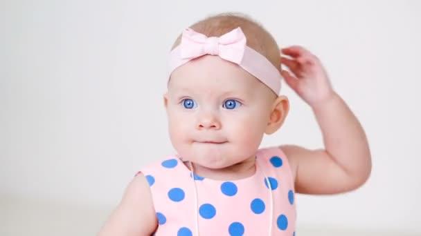 malá holčička v šatech růžový polka dot s obvazem na hlavě