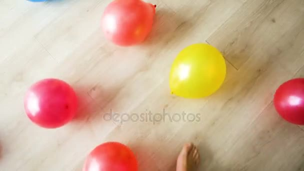 Child playing with air balloons running and kicking in the big room