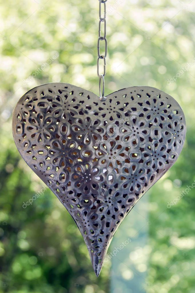 Iron heart hanging on a chain on a background of green trees and swinging