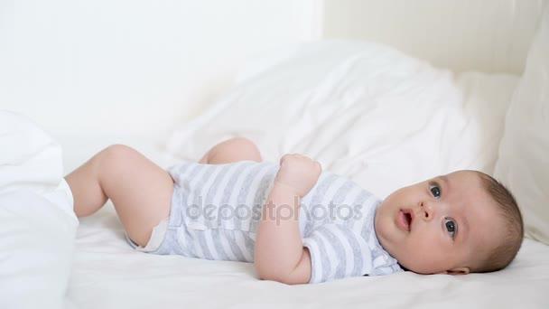 Neugeborenes liegt auf dem weißen Bett der Eltern