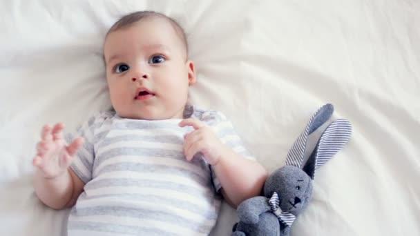 novorozence na tři měsíce, leží na zádech v bílé posteli
