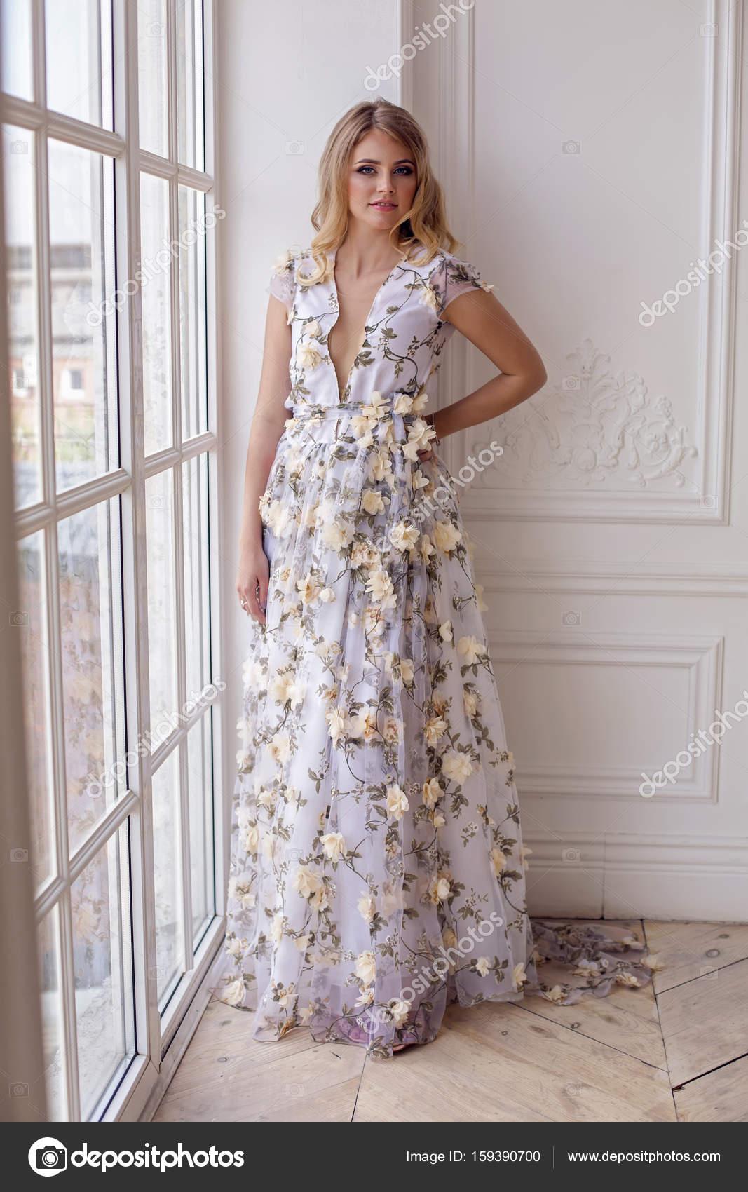 ξανθιά κοπέλα σε μια μόνιμη floral μακρύ φόρεμα — Φωτογραφία Αρχείου ... feb3b9aff30