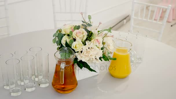table with carafes of apple and orange juice