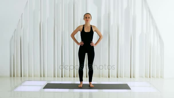 a5cbb73ed7 yoga girl in black dress is standing in a white Studio — Stock Video ...