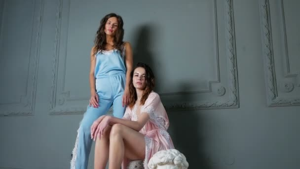 two women stand in light clothing