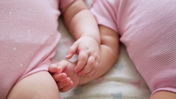 ikrek két lány egymás kezét, fekve