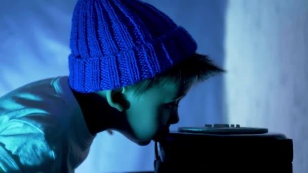 Junge mit blauem Hut und weißem T-Shirt isst eine festliche schwarze Torte