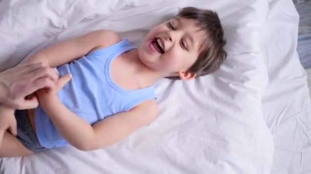 mom tickles her little son lying on the bed