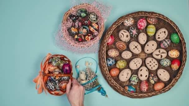 Hands holding basket with easter eggs near basket on blue background. Easter is holy. 4k