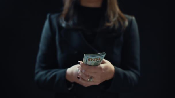 Zblízka, mladá žena podnikatel počítá peníze, na černém pozadí. 4k