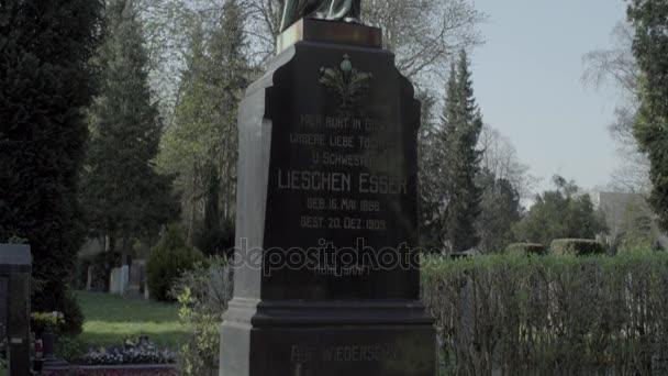 alter Grabstein aus dem 20. Jahrhundert mit einem Engel an einem sonnigen Frühlingstag. Neigung von unten nach oben. 4k in Slog3. Großer Schuss.