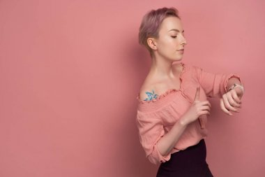 A girl with short pink hair stands in a blouse on a pink background, looks at the clock on her hand, raising her index finger up.