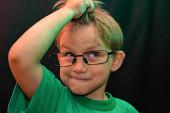 Meglepett fiú szemüvegben fekete háttér fogja a kezét a hajával, és felnéz