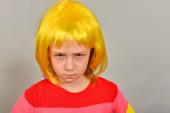 Egy sárga parókás lány egy reklámtermékre mutat, egy világos színű gyerekre szürke háttérrel..