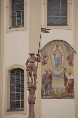 Lindlbrunnen (Lindl fountain) and east side of baroque church Saint Oswald in Traunstein, Germany