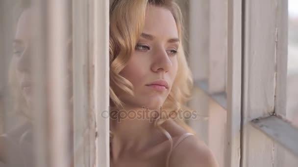 bella donna bionda in posa in studio in intimo vicino alla finestra