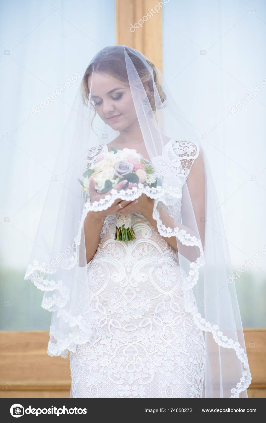 Schönheit Braut im Brautkleid mit Blumenstrauß und Spitze Schleier ...