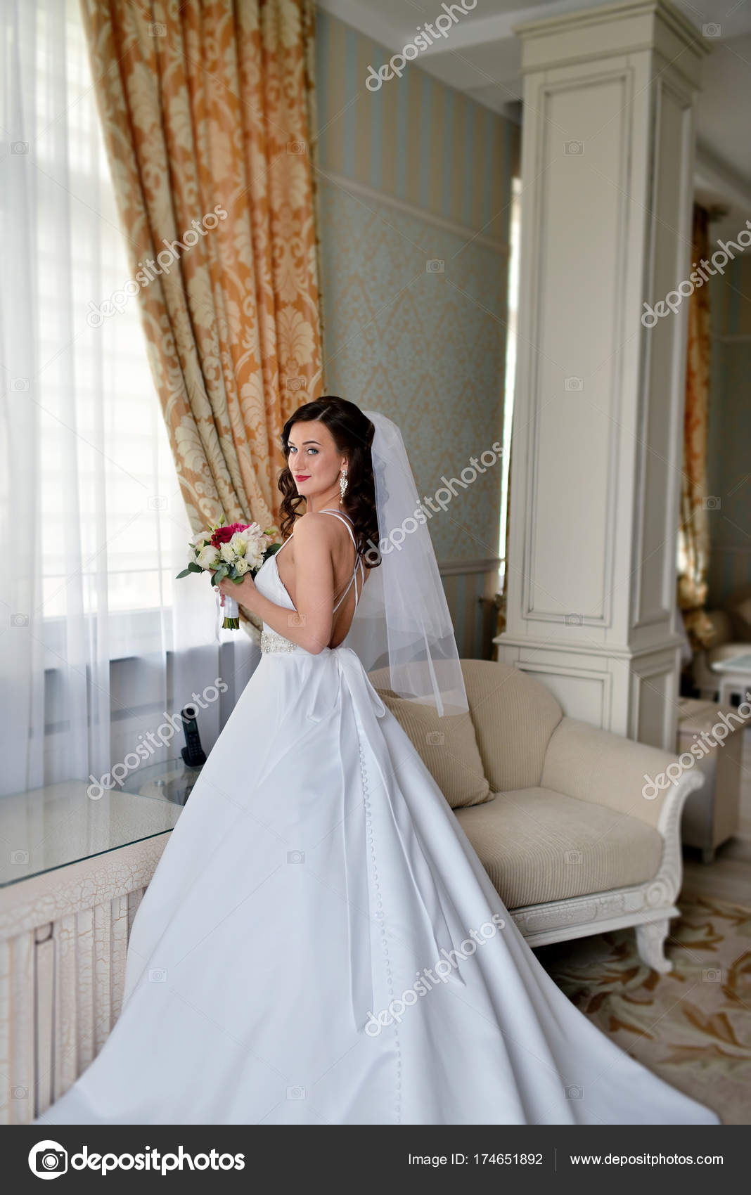 Beauty bride in bridal gown with bouquet and lace veil indoors ...