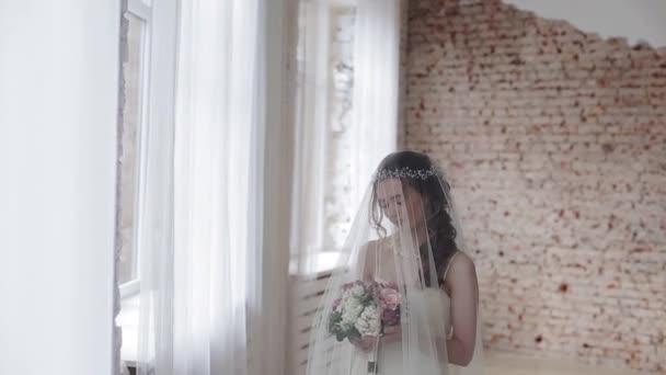krásná mladá žena nevěsty s kyticí pózuje ve studiu