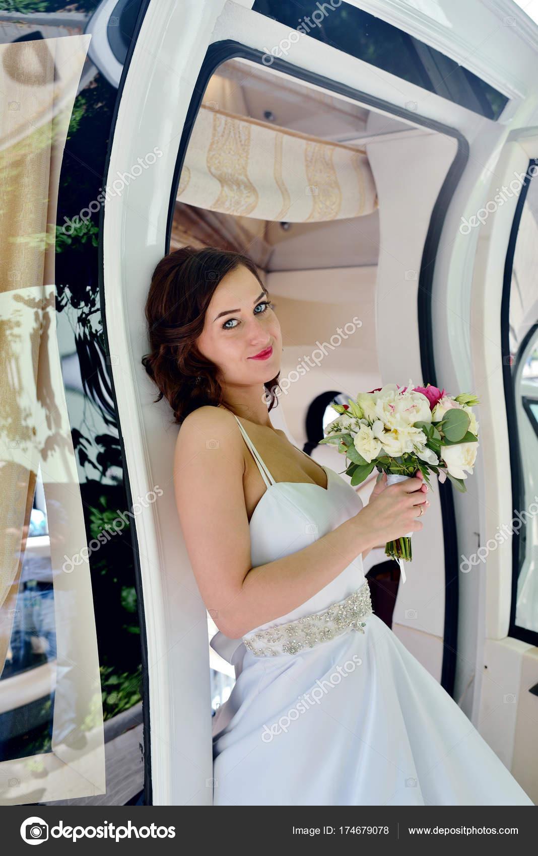 f2079b7670 Chica modelo hermosa en un vestido de novia blanco. Retrato femenino en el  auto. Mujer con peinado. Señora Linda al aire libre ...