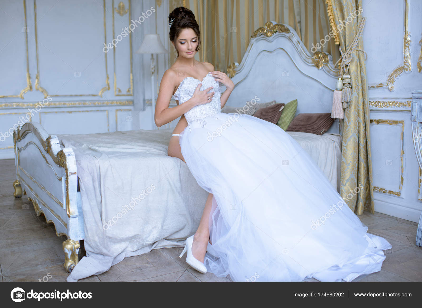 Beautiful bride in lingerie is wearing a wedding dress — Stock Photo ...
