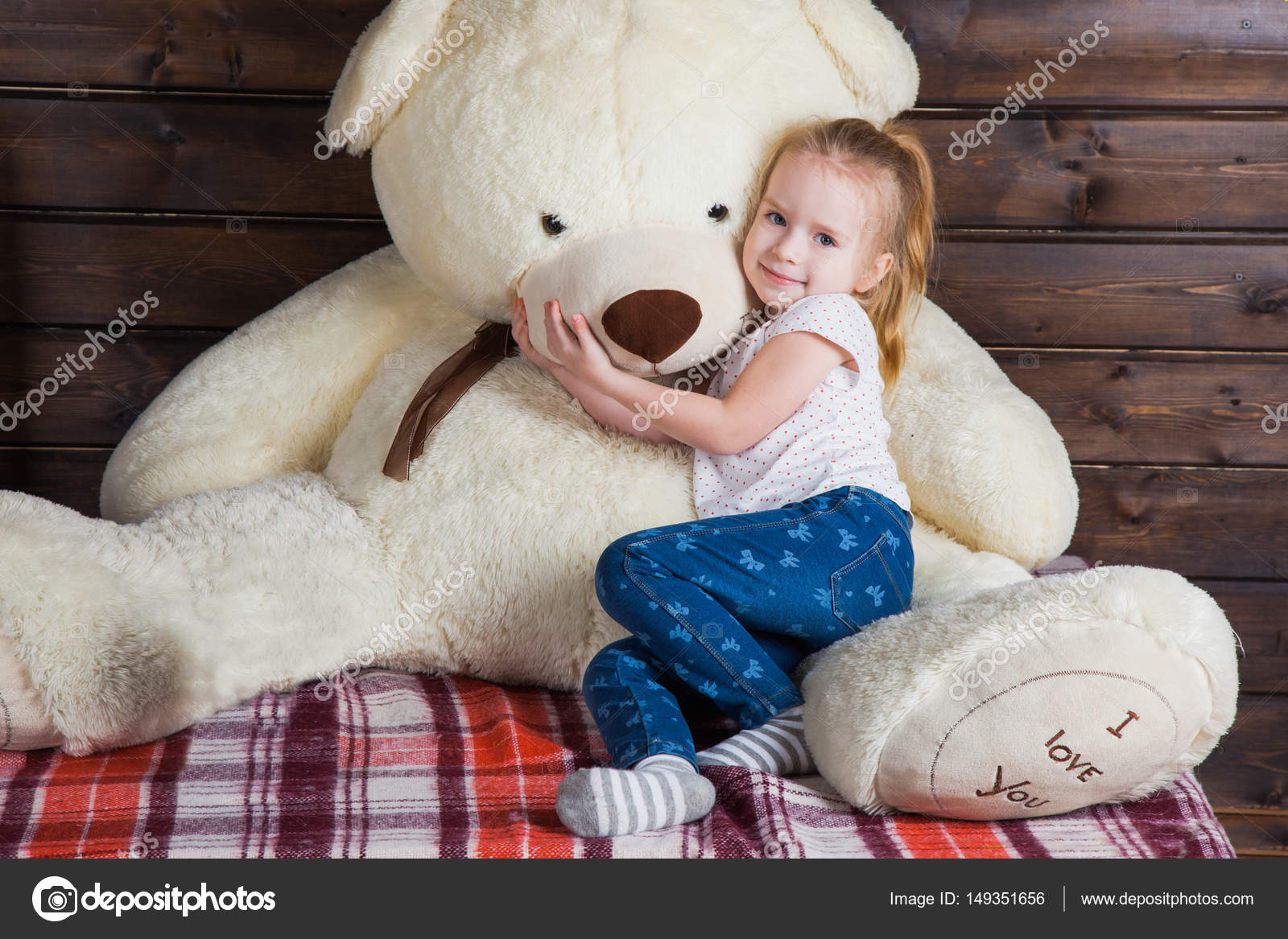cute little girl with huge teddy bear i love you text on the to