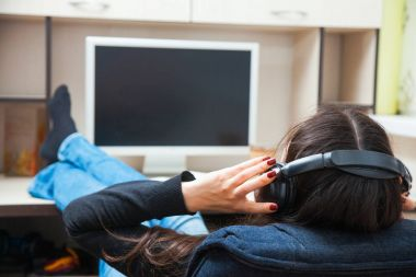 Young woman in earphones listen to music at home