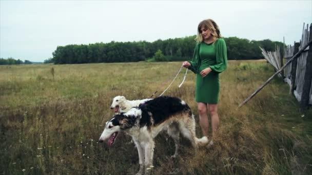 ragazza in vestito verde con due levrieri russi