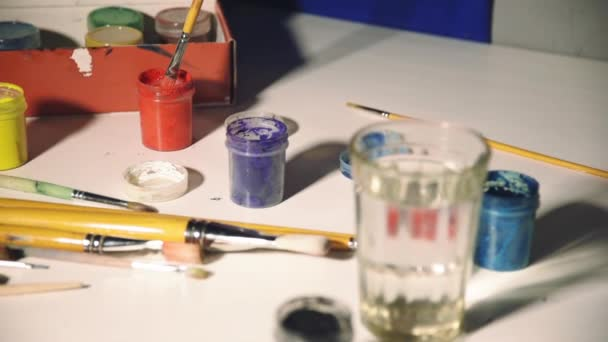 gouache different colors and a glass of water