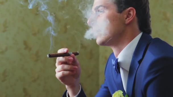 the man with the cigar blows smoke