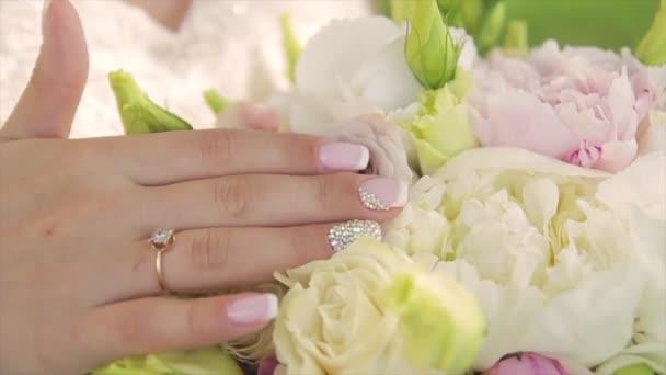 The brides hand strokes a wedding bouquet