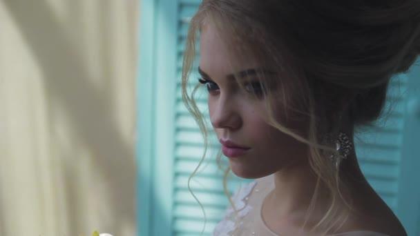 Velmi krásná blondýna s modrýma očima v bílém nevěsta šaty u okna s kyticí