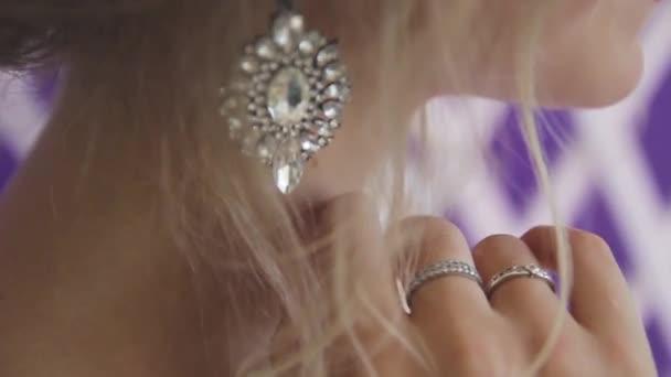Velmi krásná blondýna s modrýma očima v bílých nevěsty šaty na fialovém pozadí ve studiu