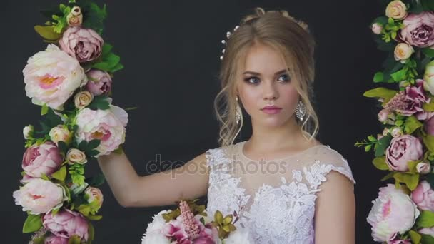 Very beautiful blonde with blue eyes in white dress a bride on a swing in studio on a black background with a bouquet of flowers