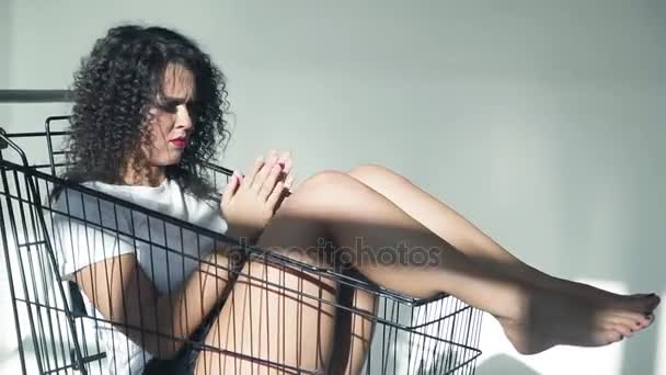 Curly beautiful girl in studio shot on a white background in a shopping cart from a supermarket