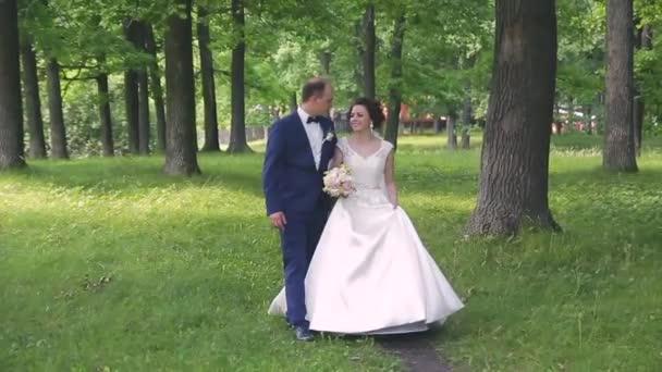 v lásce mladé svatební pár procházky v parku. Manžel s manželkou v bílých nevěsty nosí procházku v přírodě