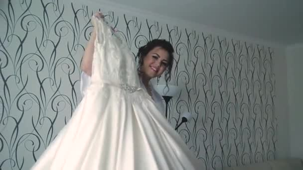 Mladá krásná šťastná nevěsta se připravuje ráno na svatbu, točí s svatební šaty