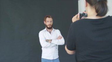 charismatic bearded young man in white shirt on black background in photo studio posing for photographer