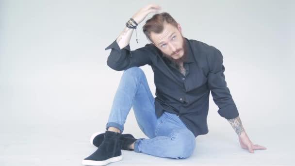 charismatischer bärtiger junger Mann in schwarzem Hemd auf weißem Hintergrund im Fotostudio, der für Fotografen posiert