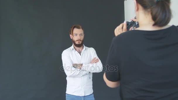 charismatische bärtiger jungen Mann in weißem Hemd auf schwarzem Hintergrund im Fotostudio posieren für Fotografen