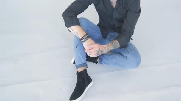 charismatische bärtiger jungen Mann im schwarzen Hemd auf weißem Hintergrund im Fotostudio posieren für Fotografen