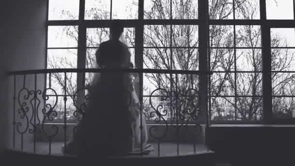 Silueta ženy proti lehké okno, svatba v černé a bílé